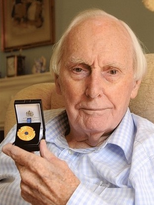 Roy Russell with the medal given to him in 2009 by then Prime Minister Gordon Brown. (Pic: Dorking Advertiser)